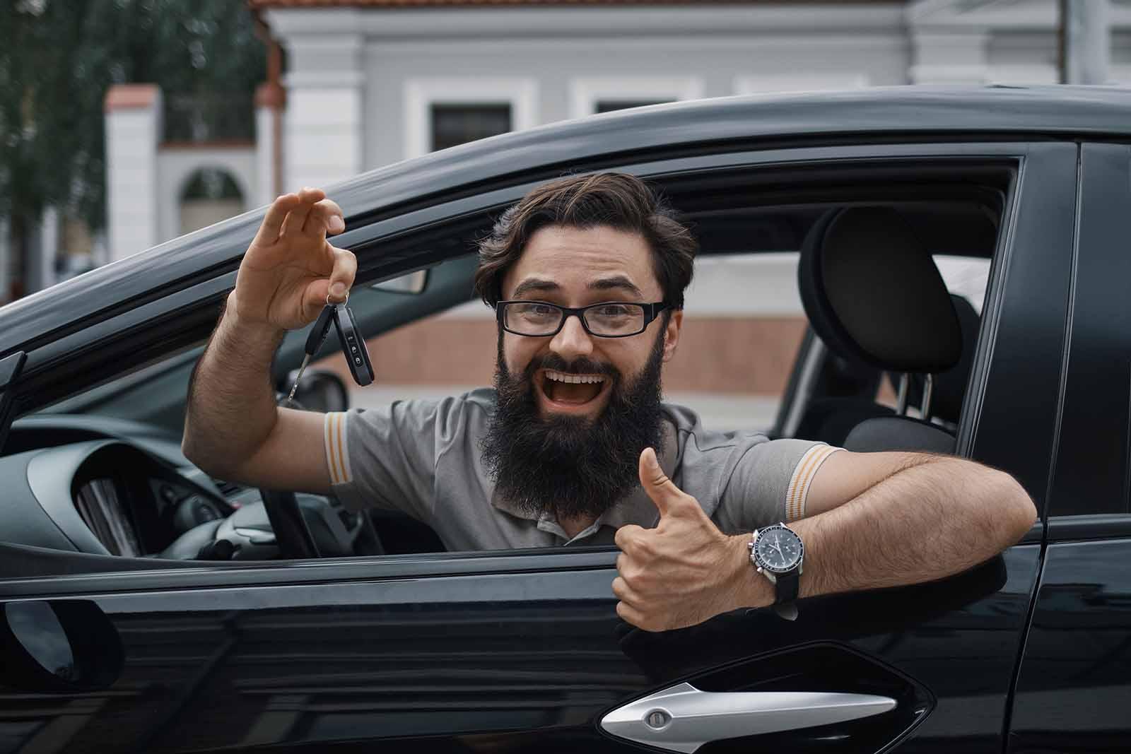 hombre de barba contento en coche